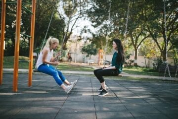 Photo of two teens talking on swings